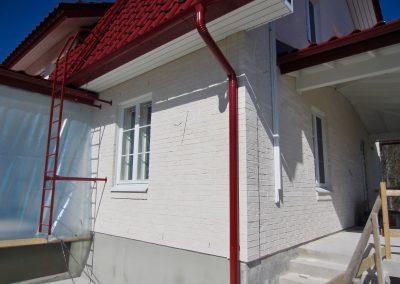 Punaista tiiltä katolla ja valkoista seinässä
